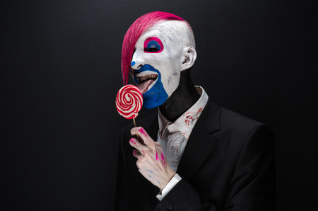 scary clown: Clown and Halloween theme: Scary clown with pink hair in a black jacket with candy in hand on a dark background