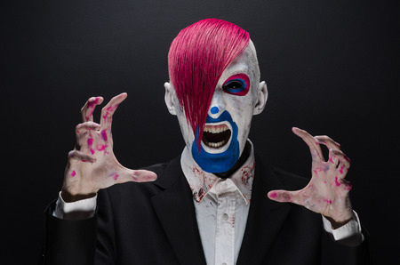 Clown and Halloween theme: Scary clown with pink hair in a black jacket on a dark background