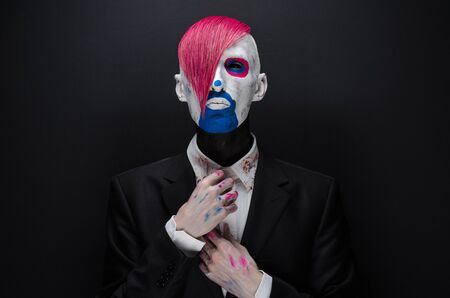 scary clown: Clown and Halloween theme: Scary clown with pink hair in a black jacket on a dark background