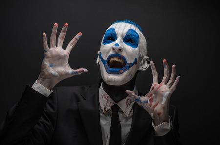 payaso terrible y Tema de Halloween: payaso loco azul en traje negro aislado en un fondo oscuro