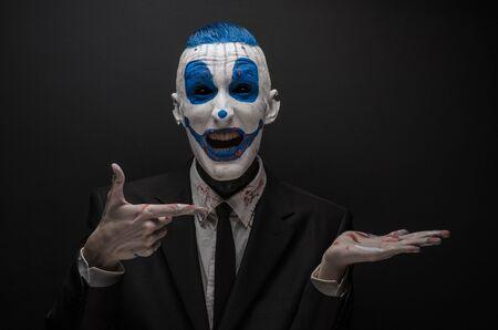ojos negros: payaso terrible y Tema de Halloween: payaso loco azul en traje negro aislado en un fondo oscuro Foto de archivo