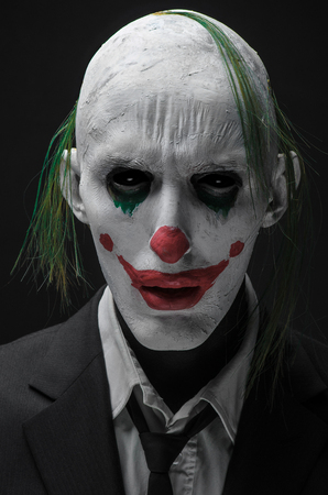 Terrible clown and Halloween theme: Crazy terrible green clown in black suit isolated on a dark background 版權商用圖片 - 56589441