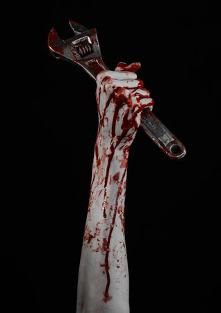 carnage: Halloween theme: bloody hand holding a big wrench on a black background studio