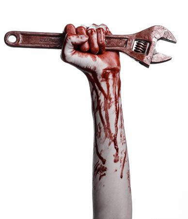 carnage: Halloween theme: bloody hand holding a big wrench on a white background studio