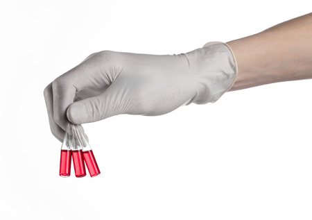specimen testing: Doctor hand holding a vial, ampule red, vaccine ampule, Ebola vaccine, flu treatment, white background, isolated, gloved hand holding a vial, cancer vaccine, a vaccine against Ebola studio Stock Photo