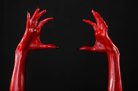 Red Devil's hands, red hands of Satan, Halloween theme, black background, isolated studio