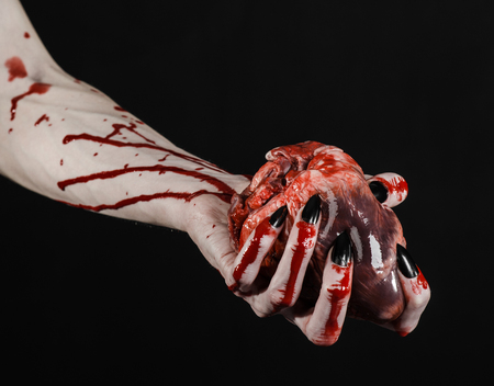carnage: Bloody horror and Halloween theme: Terrible bloody hands with black nails holding a bloody human heart on a black background isolated background