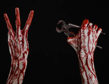 carnage: Halloween theme: bloody hand holding a pliers on a black background studio