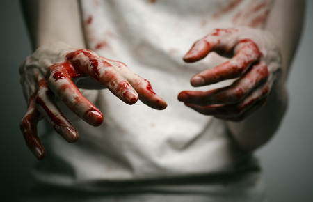 Bloody theme lone murderer: the murderer shows bloody hands and experiencing depression and pain studio Stock Photo