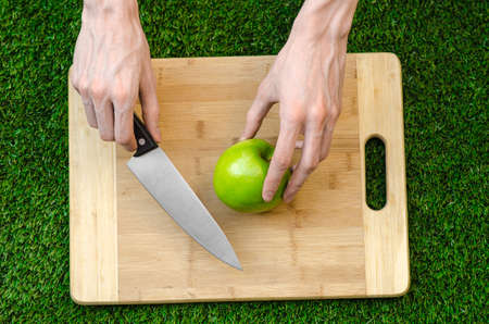 holding a knife: Vegetarians and cooking on the nature of the theme: human hand holding a knife and green apple on the background of a cutting board and green grass
