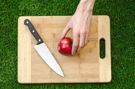 holding a knife: Vegetarians and cooking on the nature of the theme: human hand holding a knife and a red apple on the background of a cutting board and green grass Stock Photo