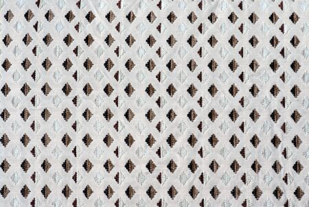 parallelogram: The texture of the fabric in the form of a brown diamond pattern is repeated on the white background studio