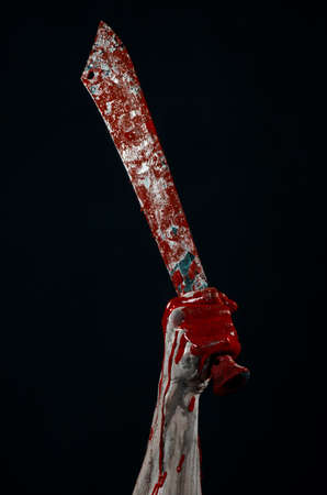machete: Bloody halloween theme: bloody hands holding a bloody machete isolated on black background in studio
