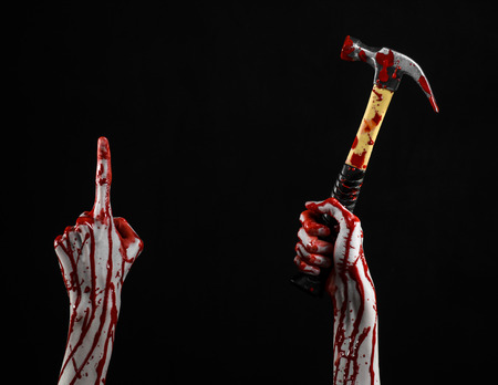 walking corpse: Bloody halloween theme: bloody hand holding a bloody hammer isolated on a black background