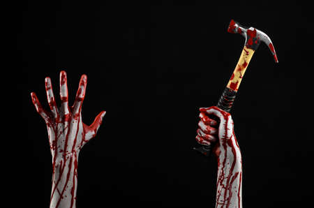 tool and die: Bloody halloween theme: bloody hand holding a bloody hammer isolated on a black background