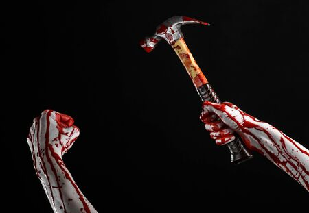 carnage: Bloody halloween theme: bloody hand holding a bloody hammer isolated on a black background