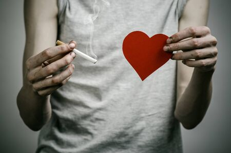 salud publica: Cigarettes, addiction and public health topic: smoker holds the cigarette in his hand and a red heart on a dark background Foto de archivo