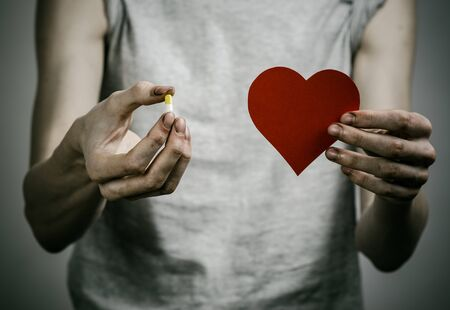 addiction alone: he fight against drugs and drug addiction topic: addict holding a narcotic pills on a dark background in studio