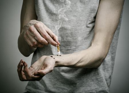public health: Cigarettes, addiction and public health topic: smoker puts his hand on the cigarette on a dark background in studio