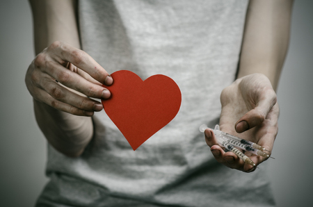 youth crime: The fight against drugs and drug addiction topic: skinny dirty addict holding a syringe with a drug and red heart on a dark background in studio