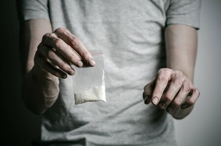 methamphetamine: The fight against drugs and drug addiction topic: addict holding package of cocaine in a gray T-shirt on a dark background Stock Photo