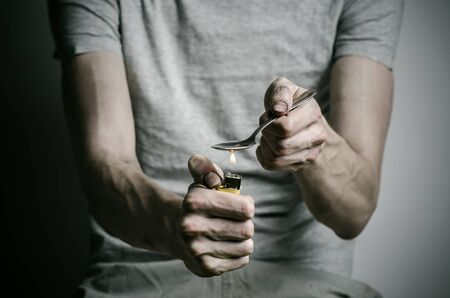 heats: The fight against drugs and drug addiction topic: addict holding spoon lighter and heats the liquid drug in a T-shirt on a dark background in studio