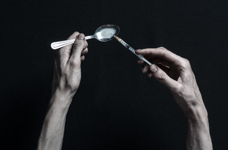 methamphetamine: The fight against drugs and drug addiction topic: hand addict lies on a dark table and around it are drugs