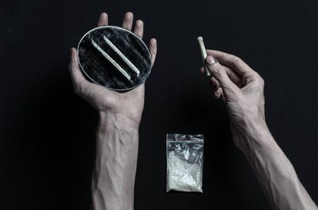 The fight against drugs and drug addiction topic: hand addict lies on a dark table and around it are drugs
