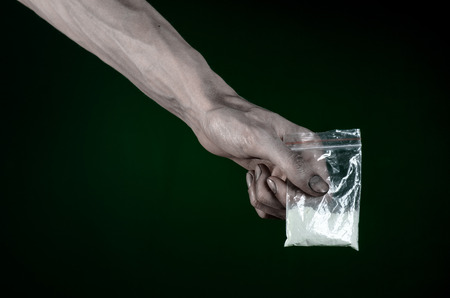 amphetamine: The fight against drugs and drug addiction topic: dirty hand holding a bag addict cocaine on a dark green background Stock Photo