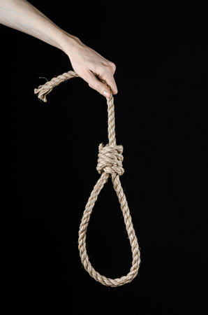 capital punishment: Lynching theme: mans hand holding a loop of rope for hanging on black isolated background studio