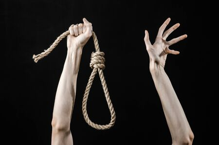 strangle: Lynching theme: mans hand holding a loop of rope for hanging on black isolated background studio