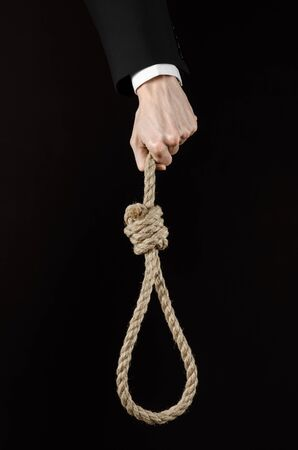 strangle: business topic: Hand of a businessman in a black jacket holding a loop of rope for hanging on black isolated background