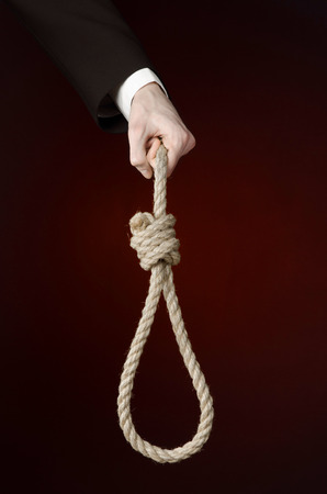 gibbet: business topic: Hand of a businessman in a black jacket holding a loop of rope for hanging on black isolated background