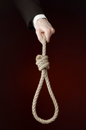 choke: business topic: Hand of a businessman in a black jacket holding a loop of rope for hanging on black isolated background