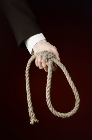 business topic: Hand of a businessman in a black jacket holding a loop of rope for hanging on black isolated background
