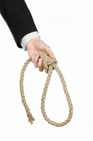 slipknot: business topic: Hand of a businessman in a black jacket holding a loop of rope for hanging on white isolated background Stock Photo