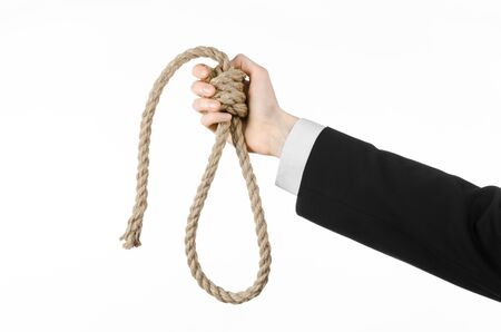 business topic: Hand of a businessman in a black jacket holding a loop of rope for hanging on white isolated background Stock Photo