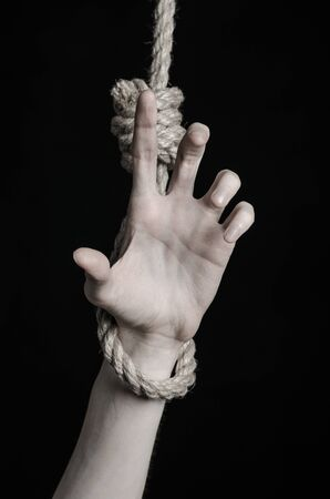 gibbet: depression topic: human hand hanging on rope loop on a black background