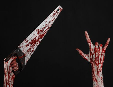 Halloween theme: bloody hand holding a bloody saw on a black background Stock Photo