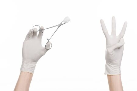 hemorragia: Surgery and medicine theme: doctors hand in a white glove holding a surgical clamp with swab isolated on white background in studio Foto de archivo