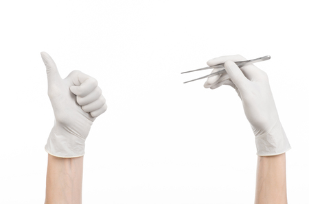 white glove: Medicine and Surgery theme: doctors hand in a white glove holding tweezers isolated on white background