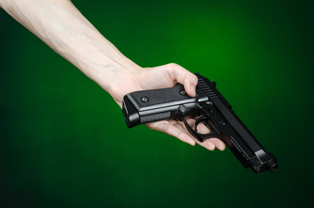 mugger: Firearms and murderer topic: human hand holding a gun on a dark green background isolated