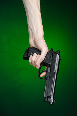 murderer: Firearms and murderer topic: human hand holding a gun on a dark green background isolated