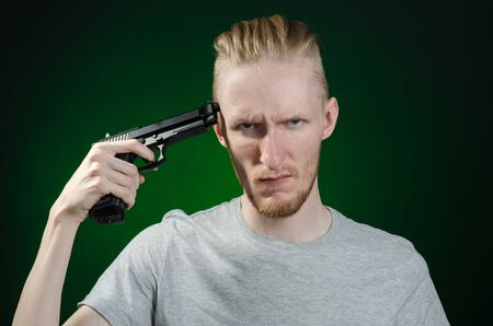 murderer: Firearms and murderer topic: suicide in a gray t-shirt holding a gun on a dark green background isolated