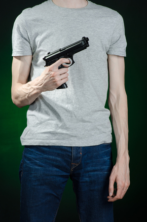 firearms: Firearms and murderer topic: man in a gray t-shirt holding a gun on a dark green background isolated