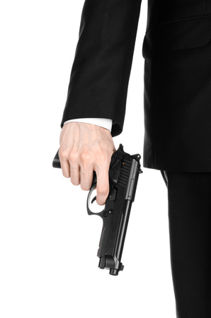 firearms: Firearms and security topic: a man in a black suit holding a gun on an isolated white background