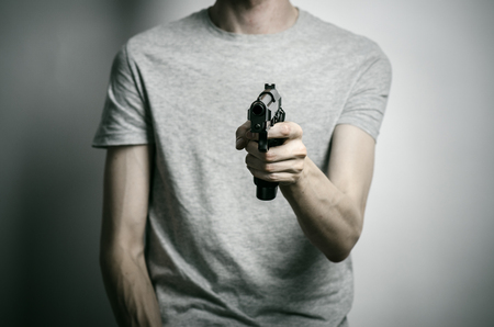 firearms: Horror and firearms topic: suicide with a gun on a gray background
