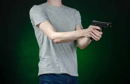 mugger: Firearms and murderer topic: man in a gray t-shirt holding a gun on a dark green background isolated