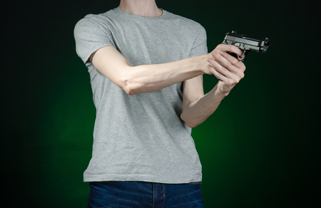 murderer: Firearms and murderer topic: man in a gray t-shirt holding a gun on a dark green background isolated
