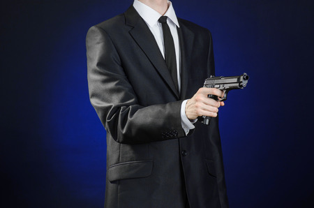 firearms: Firearms and security topic: a man in a black suit holding a gun on a dark blue background in studio Stock Photo